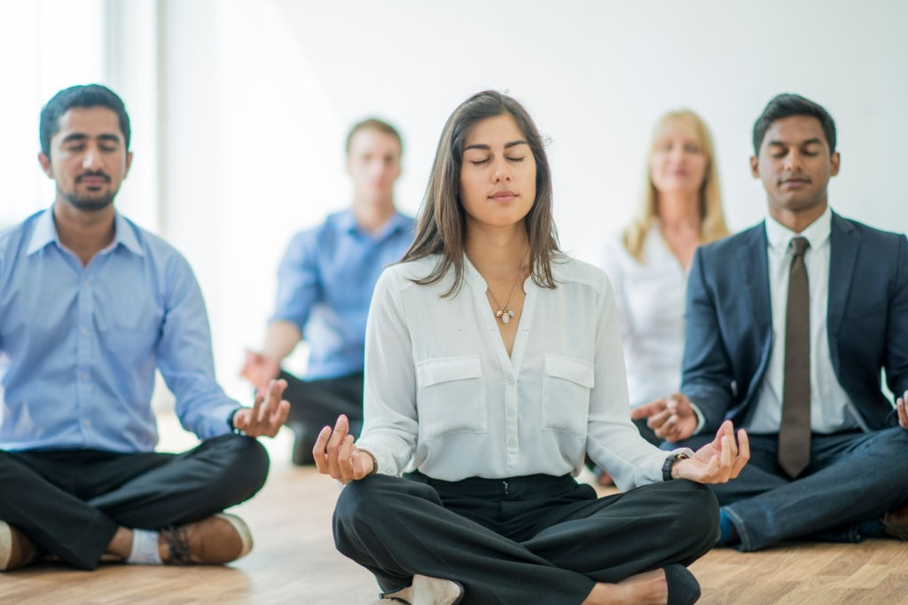 A multi-ethnic group of young business men and women in semi-casual office clothes are sitting on the floor and meditating to relax in an indoor, sunlit office.